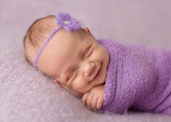 Новонароджена дитина посміхається