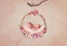 Новонароджена дівчинка на квітковій гойдалки