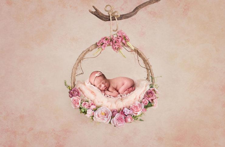 Новорожденная девочка на цветочной качели