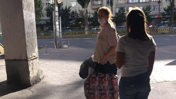 Женщина несет своего ребенка в пакете
