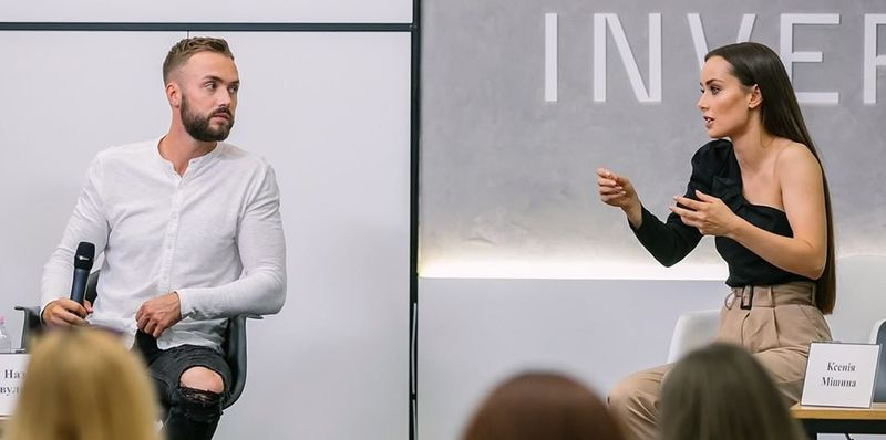 Штани кольору беж і асиметрична чорна блуза з відкритим плечем для обговорення