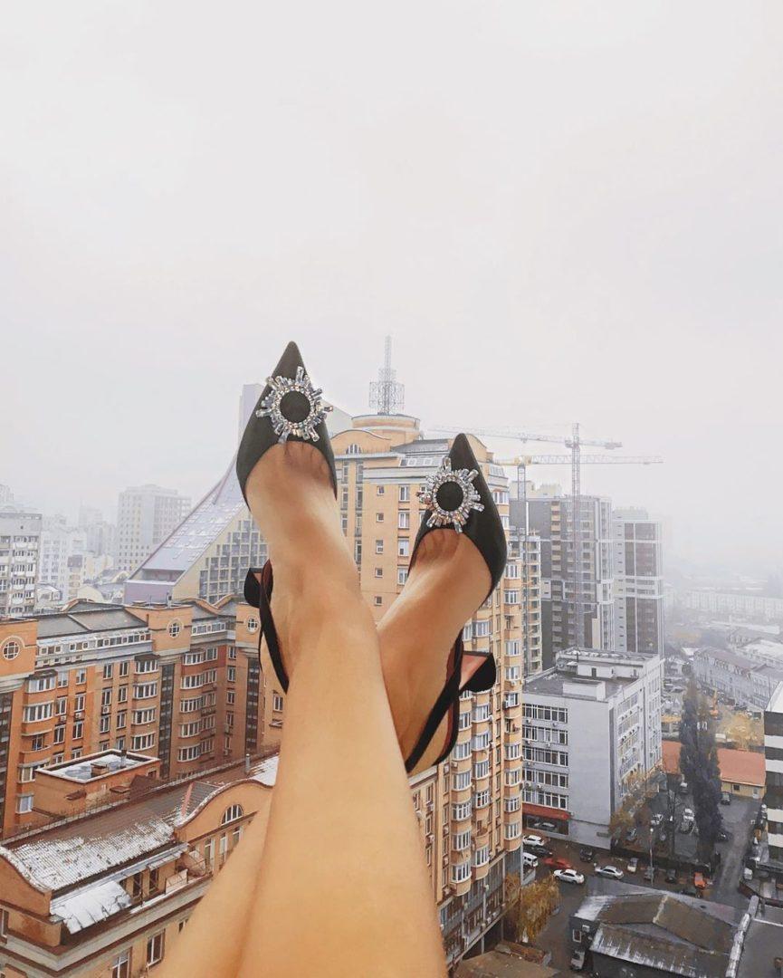 Ноги Леси Никитюк на фоне пейзажей Киева