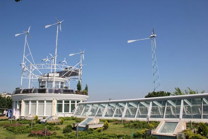 Ветровая электростанция во дворе, сбоку - крыша подземного бассейна