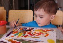 Мальчик рисует карандашом