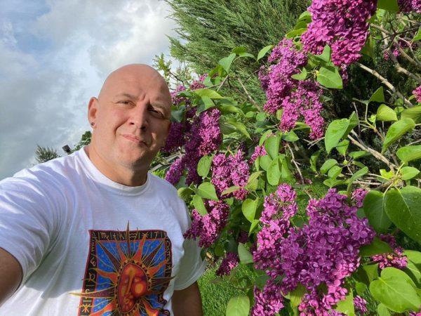 Потап показал цветущие кусты сирени в своем дворе во время прогулки с Настей